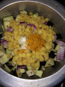 Put brinjal, onion, toor dal, sambar powder and salt. Add half glass of water.