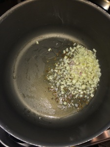 Let the cumin splutter. Add finely chopped garlic.