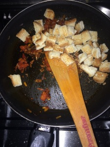Allow the raw smell of the red chili powder to go and then add the bread pieces, mix well.