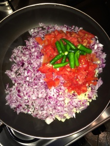 Add the chopped onion, garlic, tomato and green chilies.