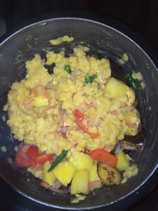 Transfer the sautéed vegetables into a pressure cooker and add half the cooked toor dal.