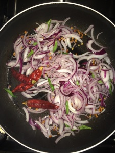 Add dry red chilies and chopped onion and saute for a while.