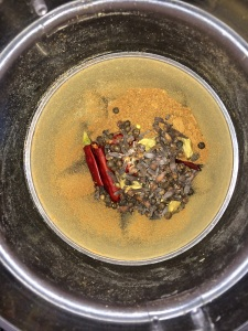 Then add the dry roasted red chilies, pepper, cardamom and cloves together and grind them in the blender.