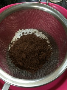 Place a sieve on top of the bowl and add all the dry ingredients(flour,cocoa, baking soda, baking powder and salt) to it.