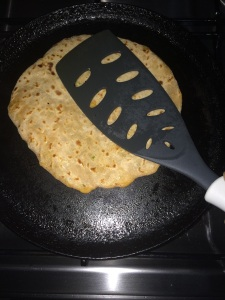 Smear oil on the other side of the paratha also and cook with pressure using the ladle.