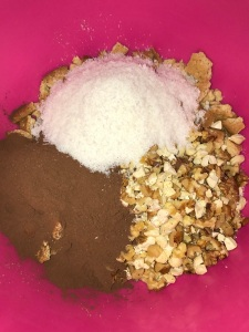 Now add the nuts, desiccated coconut and cocoa powder to the biscuits.